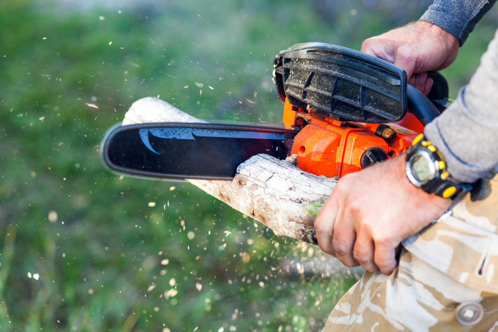 человек режет электропилой цепной дрова